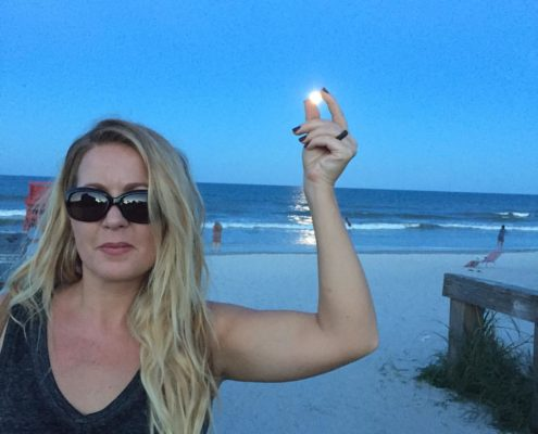 Abby Hinote capturing the full moon between her left hand on Jacksonville Beach, Florida